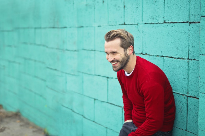 man wearing a red sweater leaning on a wall while smiling, bipolar signs and symptoms, bipolar disorder treatment facilities