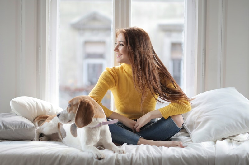 cheerful lady sitting on a bed with pet dog, how to heal loneliness, ways to fight depression, fighting depression
